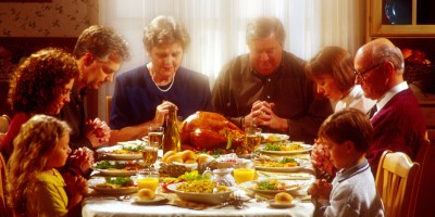 Family praying together over Thanksgiving dinner